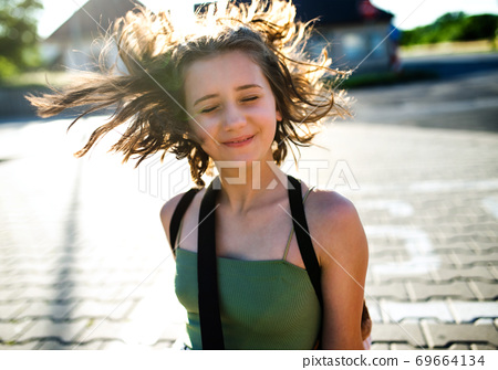 Portrait of teenager girl walking outdoors in city, having fun. 69664134