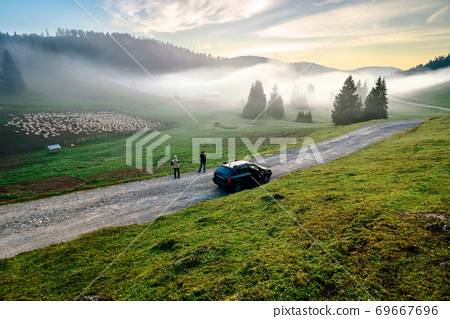morning mist in apuseni natural park. valley full of fog at dawn. beautiful landscape of romania mountains in autumn. flock of sheep on the meadow. spruce trees on the hills. glowing clouds on the sky 69667696