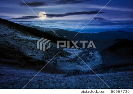 hills and valley of mountain landscape at night. clouds on the deep blue sky. beautiful scenery of chornohora ridge in full moon light 69667730