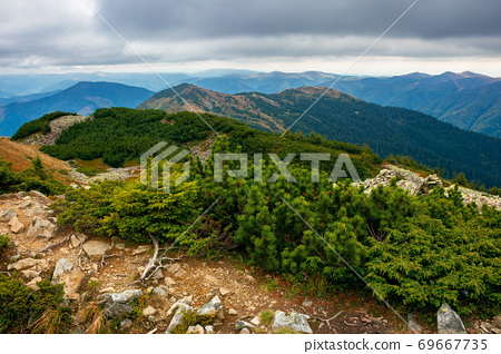 view from the top of a mountain. cloudy autumn scenery. mountain range behind the valley in the distance. dramatic weather in colorful scenery 69667735