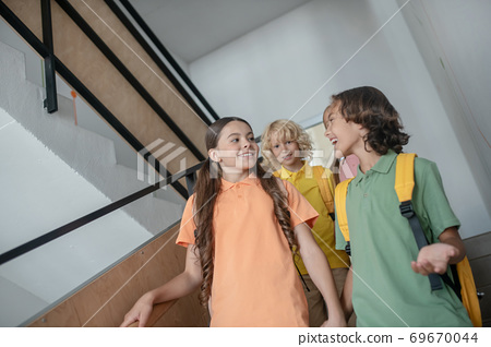 School friends going downstairs and talking and feeling good 69670044