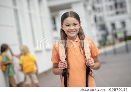 Cute girl in orange tshirt smiling nicely and feeling good 69670115