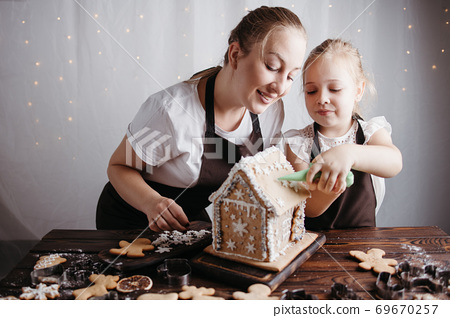 Mother and daughter decorating gingerbread house 69670257