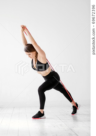 Athletic woman working out with power band 69672396