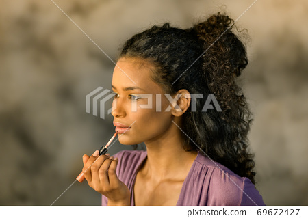 Attractive Dominican girl applying her makeup 69672427