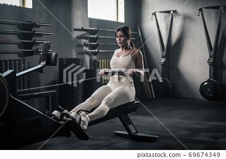 Woman in Uniform Has Training on Rowing Machine . 69674349