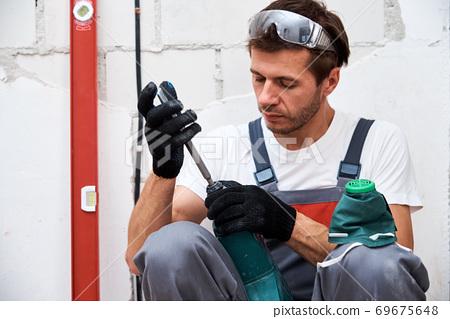 Man worker using hammer drill, closeup. Renovation concept 69675648