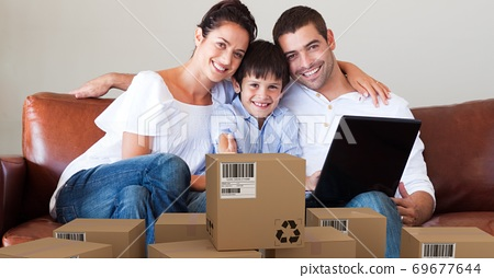 Caucasian couple and their son using laptop shopping online with a pile of boxes 69677644