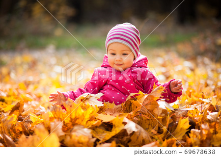 Little kid is playing and sitting in fallen leaves in autumn par 69678638