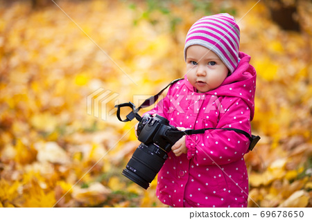 Little kid is playing with camera and taking photo of autumn nature as master. Baby is in autumn park 69678650