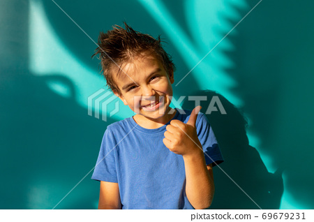 Portrait of a funny brunette boy in a blue shirt. thumbs up. turquoise background. Education. Looking and smiling at the camera, toddler, preschooler 69679231