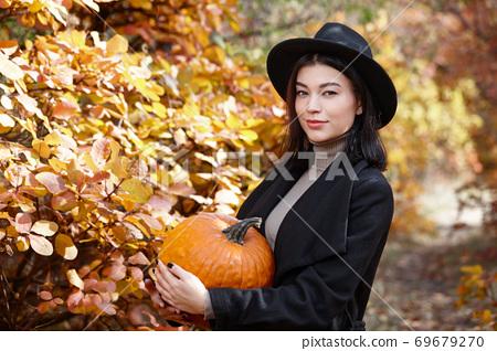 Woman in black with Halloween pumpkin 69679270