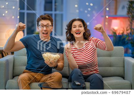 couple with popcorn sitting on sofa 69679487