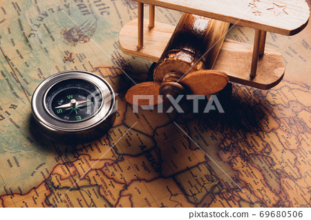 Old compass discovery and wooden plane on vintage paper antique world map 69680506