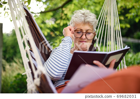 Portrait of active senior woman working outdoors in garden, home office concept. 69682031