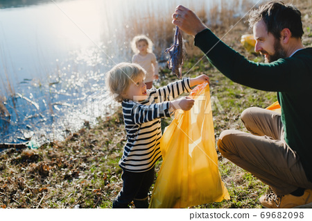 Father with small kids collecting rubbish outdoors in nature, plogging concept. 69682098