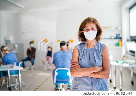 Portrait of old woman with face mask waiting, coronavirus, covid-19 and vaccination concept. 69682644