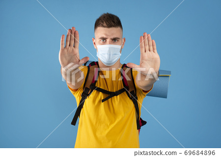 Funky young tourist with backpack wearing protective mask and showing STOP gesture over blue studio background 69684896