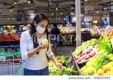 Asian woman wearing protective face mask push and hold shopping cart in supermarket department store. Girl, looking grocery to buy  some fruit. New normal after covid-19. Family concept. 69685494