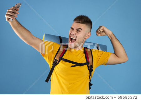 Cool young guy with tourist equipment taking selfie on smartphone over blue studio background 69685572
