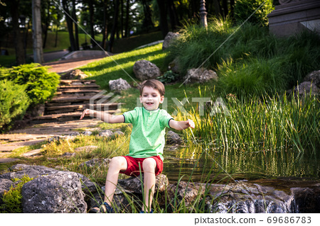 A young boy sits on the river bank, view from top. Warm summer or spring day Cute Caucasian kid play 69686783