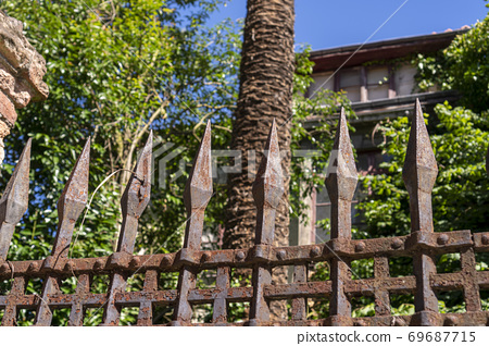 Rusty metal fence with peaks in front of a garden with an abandoned house and trees and thickets. Dramatic landscape 69687715