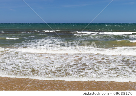 Stunning view of the ocean calm surf with quiet waves reaching the sandy shore and clear turquoise water and clear skies. Tourist's dream 69688176