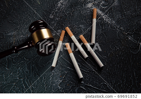 Judge gavel and five cigarettes on grey background. Tobacco law 69691852