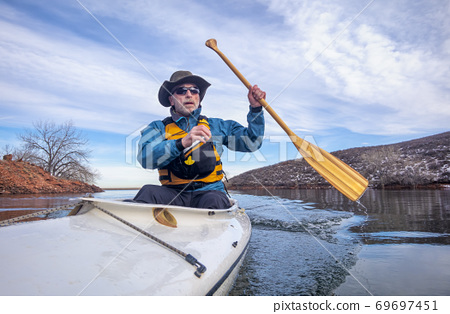 senior male is paddling expedition canoe 69697451
