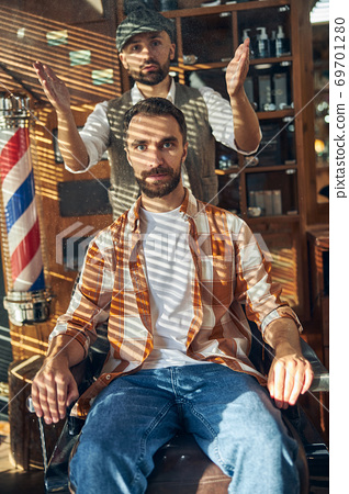 Stylish barber and hipster client posing at a barbershop 69701280
