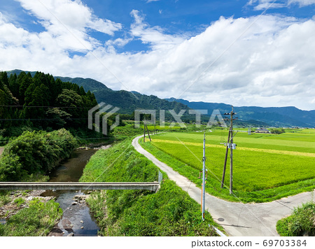 Summer rural scenery of Minamiaso seen from a trolley train 69703384