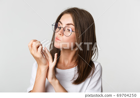 Close-up of attractive young brunette woman in glasses looking at fingernails after beauty salon 69704250
