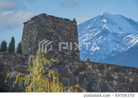 tower on the background of the caucasus mountains. 69706350