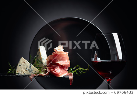 Glass of red wine with traditional mediterranean snacks. 69706432