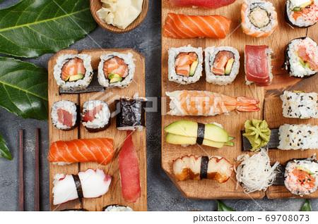 Sushi Set nigiri and sushi rolls on rectangular wooden plates 69708073
