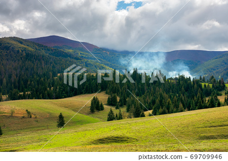 autumnal countryside landscape. beautiful mountain scenery on a cloudy day. green fields rolling through hills in to the forest at the foot of the ridge 69709946
