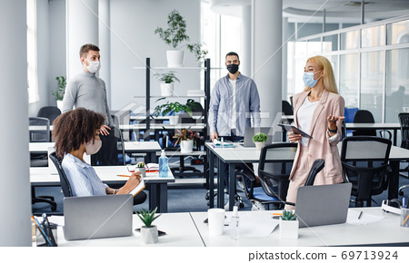 Meeting in office and instructions from boss. Young business woman in protective mask with tablet in hand speaks to workers at workplace 69713924