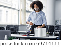 Disinfection from coronavirus in coworking place. African american young woman in protective mask working in office, cleans laptop with antiseptic spray in interior 69714111