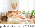 Young beautiful girl having relaxed morning in bed 69714149