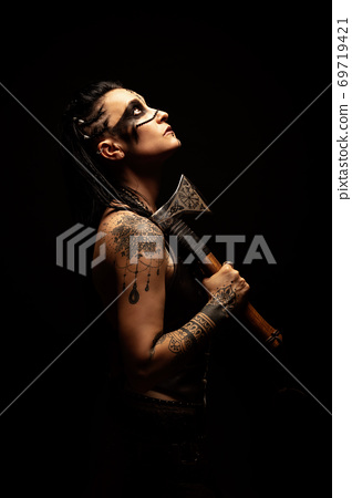Portrait of a young tattooed Viking warrior with an ax on her shoulder 69719421