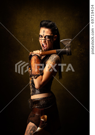 Portrait of a young tattooed Viking warrior, screaming, ax on shoulder 69719434