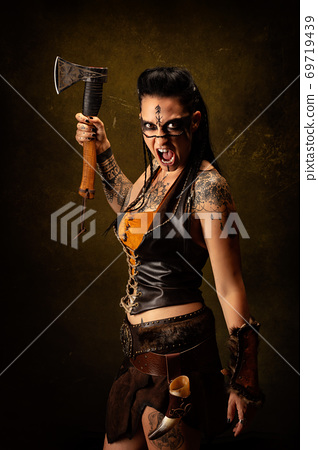 Portrait of a young tattooed Viking warrior, screaming, an ax in her hand 69719439