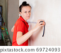 A woman in the room makes a measurement of the drywall wall using a measuring tape for subsequent wallpapering. 69724093