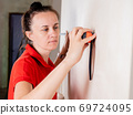 A woman in the room makes a measurement of the drywall wall using a measuring tape for subsequent wallpapering. 69724095