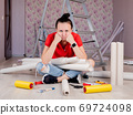 Preparing for wallpapering in the room. A sad woman is sitting on the floor with rolls of Wallpaper in her hands. 69724098