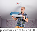 A happy man on a stepladder is going to install an led ceiling light. 69724103