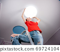 Installing a ceiling light in the children's room. Woman sets the ceiling lamp on the ceiling. 69724104