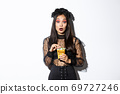 Image of amazed asian woman in witch halloween costume looking at camera while holding sweets in trick or treat bag, standing over white background 69727246