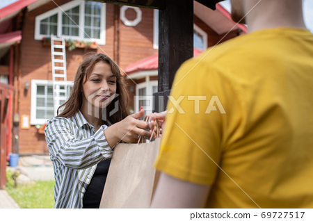 Happy woman receiving order from delivery man in front of house, shipping 69727517