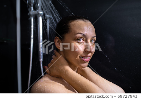 smiling nude young woman enjoying flowing water taking shower looking at camera 69727943